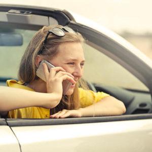 Junge Frau mit Führerschein in neuem Auto