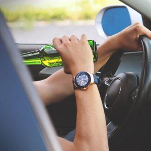 Junger Mann trinkt im Auto