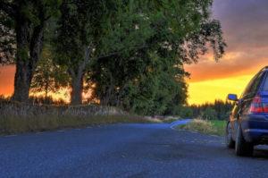 Auto auf einer Landstraße in Schweden bei Sonnenuntergang